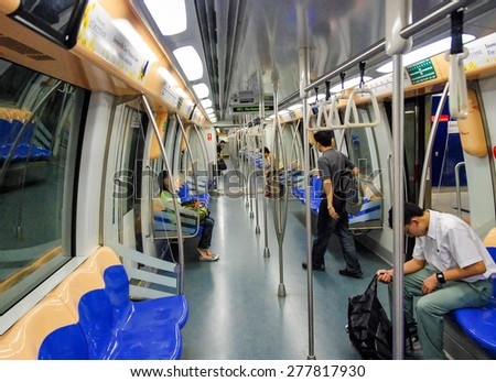 SINGAPORE - JULY 12, 2008: People on the subway. Underground system serves more than 2 million people daily. - stock photo
