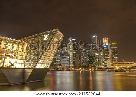 SINGAPORE - JULY 14: Wonderful cityscape of Singapore, July 14, 2014, Singapore. Louis Vuitton shop on the water at Marina bay and skyscrapers behind. - stock photo