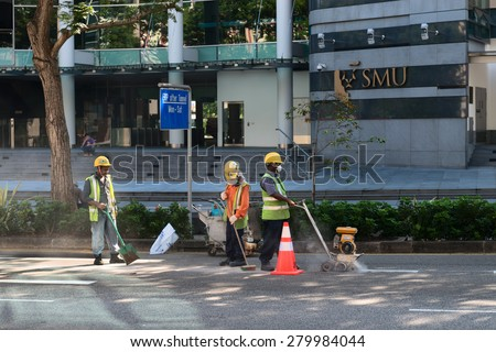 SINGAPORE - 02 JUN 2013: Construction workers use specialized equipment to cut a section of pavement on a downtown street. - stock photo