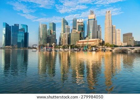 SINGAPORE - 01 JUN 2013: Stunning city skyline on a clear day, with its modern highrise towers, reflected in the calm water of the bay. - stock photo