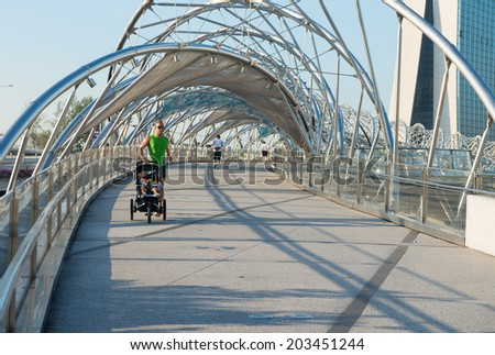 SINGAPORE - JUNE 01, 2013: Man goes for a morning jog on Helix bridge with a kid. It is a pedestrian bridge in the Marina Bay area in Singapore. It was opened on 24 April 2010. - stock photo