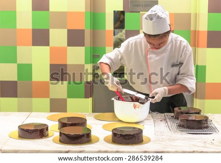 SINGAPORE - JUNE,12: Unidentified woman chef in white uniform prepares  the Chocolate cakes in the colorful kitchen . SINGAPORE JUNE,12 2015 - stock photo