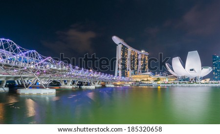 SINGAPORE - March  27: Helix Bridge and marchMarina Bay Sands on July 27, 2014. At night, the Helix Bridge is illuminated by a series of lights creating a special visual experience for the visitors. - stock photo