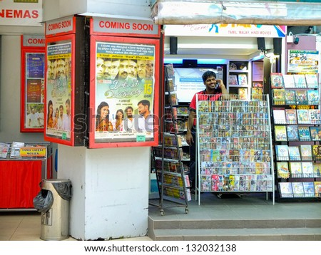 SINGAPORE - MARCH 8: Indian movie poster next to shop selling movie DVDs on March 8, 2013 in Singapore. Rex Cinema is one of Singapore's oldest, now specialising in screening Bollywood blockbusters. - stock photo