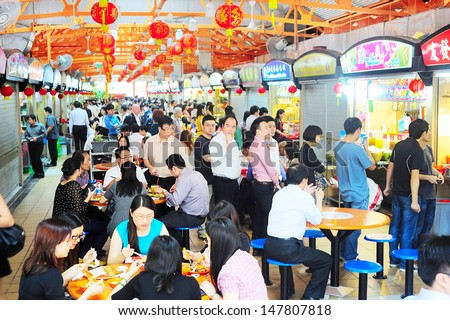SINGAPORE - MARCH 6: Locals eat at a popular food hall on March 06, 2013 in  Singapore. Inexpensive food stalls are numerous in the city so most Singaporeans dine out at least once a day.  - stock photo
