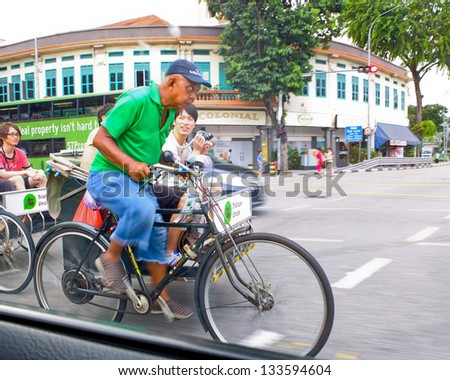 SINGAPORE - MARCH 3: Man pedalling a rickshaw carrying tourists on March 3, 2013 in Singapore. Singapore was the first city to use cycle rickshaws on large scale, now used by tourists for city tours. - stock photo