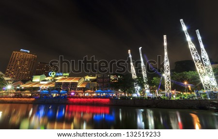 SINGAPORE - MARCH 02: Night shot of Clarke Quay at night over river in Singapore. Illuminated building of popular meeting place. At left side in background are hotels.March 2, 2013 in Singapore.