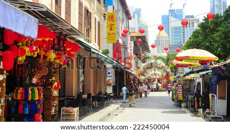 SINGAPORE - MARCH 5, 2013: Shoppers walking on Chinatown street in Singapore. The city state's ethnic Chinese began settling in Chinatown circa 1820s.  - stock photo