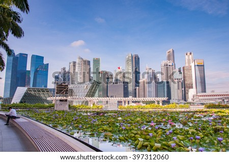 Singapore-March 12,2016 : Singapore skyline of business district and Marina Bay in day, foreground with lotus pond and man - stock photo