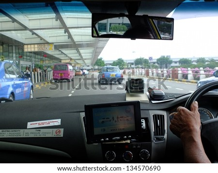 SINGAPORE - MARCH 9: Taxi driver arriving at international airport on March 9, 2013 in Singapore. Singapore airport is the main aviation hub in Southeast Asia, handling 66 million passengers per year. - stock photo