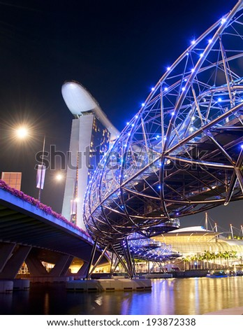 SINGAPORE - MARCH 06, 2013:  The Helix Bridge and Marina Bay Sands at night.  The Helix is fabricated from 650 tonnes of Duplex Stainless Steel and 1000 tonnes of carbon steel.  - stock photo