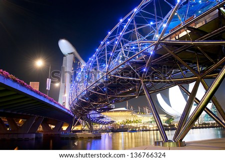 SINGAPORE - MARCH 06:  The Helix Bridge and Marina Bay Sands on March 06, 2013 in Singapore.  The Helix is fabricated from 650 tonnes of Duplex Stainless Steel and 1000 tonnes of carbon steel. - stock photo