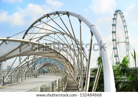 SINGAPORE - MARCH 08: The Helix Bridge on March 08, 2013 in Singapore. Is a bridge in the Marina Bay. The Helix is fabricated from 650 tonnes of Duplex Stainless Steel and 1000 tonnes of carbon steel. - stock photo