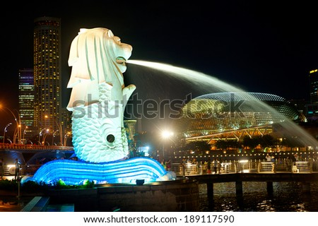 SINGAPORE - MARCH 07, 2013 : The Merlion fountain spouts water in front of Singapore downtown in Singapore. Merlion is an imaginary creature , often seen as a symbol of Singapore  - stock photo