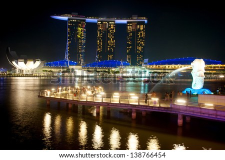 SINGAPORE - MARCH 08:  The Merlion fountain spouts water in front of the Marina Bay Sands hotel on March 08, 2013 in Singapore. Merlion is an imaginary creature , often seen as a symbol of Singapore - stock photo