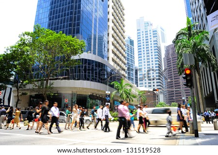 SINGAPORE - MARCH 07: Unidentified businessmen crossing the street on March 7, 2013 in Singapore. There are more than 7,000 multinational corporations from US States, Japan and Europe in Singapore - stock photo