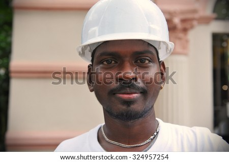 SINGAPORE - MAY 10: A migrant worker poses for a photo on a city centre construction site on May 10, 2013 in Singapore. The SE Asian city state has a significant migrant worker population. - stock photo
