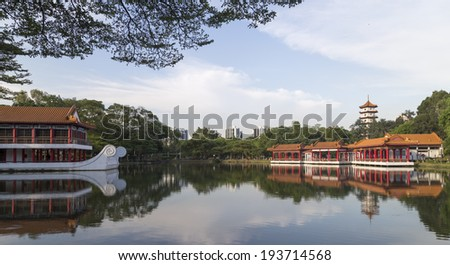 SINGAPORE - MAY 15, 2014: Chinese design covered walkway and floating tea house beside lake in Singapore Chinese Gardens