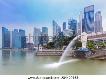 SINGAPORE, MAY 24: Merlion of Singapore by morning, business buildings in the background on May 24, 2015 in Singapore. Merlion is a mythical creature with the head of a lion and the body of a fish - stock photo