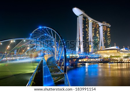 SINGAPORE - MAY 03, 2013 : The Helix Bridge and Marina Bay Sands in Singapore. The Helix is fabricated from 650 tonnes of Duplex Stainless Steel and 1000 tonnes of carbon steel.  - stock photo