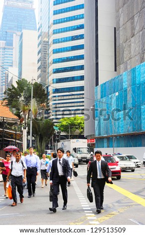 SINGAPORE - MAY 3: Unidentified businessmen crossing the street on May 03, 2012 in  Singapore. There are more than 7,000 multinational corporations from United States, Japan and Europe in Singapore.