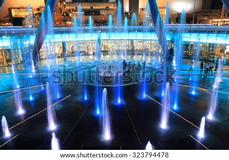 SINGAPORE - 27 MAY, 2014: Unidentified people watch Suntec City Fountain of Wealth light show. The Fountain of Wealth is listed by the Guinness Book  in 1998 as the largest fountain in the world.  - stock photo