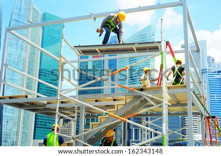 SINGAPORE - MAY 09: Workers at construction site in front of Singapore downtown on May 09, 2013 in Singapore. Construction industry is expected to pull in some $30 billion this year  - stock photo