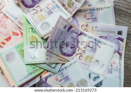 Singapore money on the gray wooden background, various of singapore dollar banknote