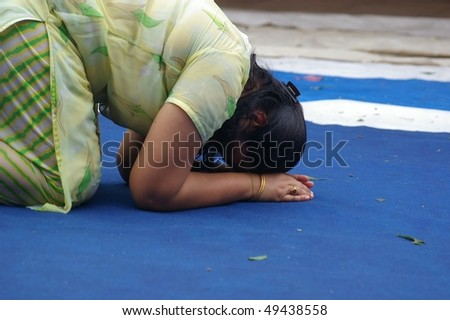 SINGAPORE - NOVEMBER 04: Hindus doing ritual prostrating at Sri Mariamman Temple for the Thimithi Festival  November 04, 2009 in Singapore. - stock photo