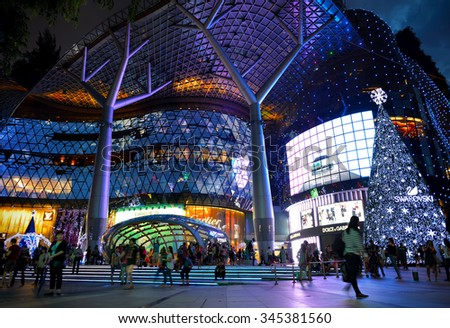SINGAPORE- NOVEMBER 29, 2015: Night view of Christmas Decoration at Singapore Orchard Road. The street with colourful christmas trees, bells, baubles, ball, ribbon, star & dressed-up shopping centres. - stock photo