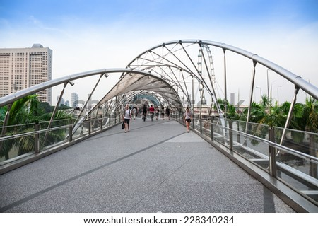 SINGAPORE - NOVEMBER 1: The Helix Bridge links the Marina Center & Bayfront areas, completing the 3.5km long walking route around Marina Bay on November 1, 2014 in Singapore.   - stock photo