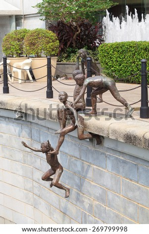 """SINGAPORE - OCTOBER 12, 2012: Bronze sculpture of the """"First Generation"""" statue of kids jumping to the river in front of the Fullerton Hotel by Chong Fah Cheong on October 12, 2012 in Singapore - stock photo"""