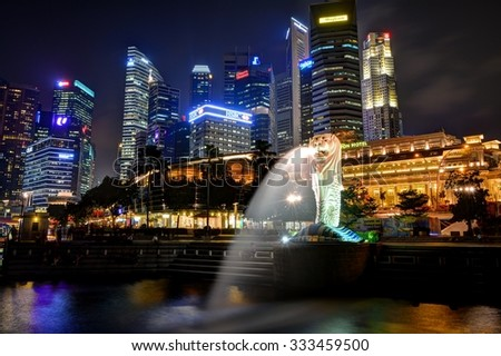 SINGAPORE - OCTOBER 20,2015: Financial district skyscrapers and Merlion at Marina bay. The Merlion is a traditional creature with a lion head and a body of a fish, seen as a symbol of Singapore. - stock photo