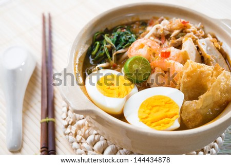Singapore prawn mee or prawn noodles. Famous Singaporean food spicy fresh cooked har mee in clay pot with hot steam. Asian cuisine. - stock photo
