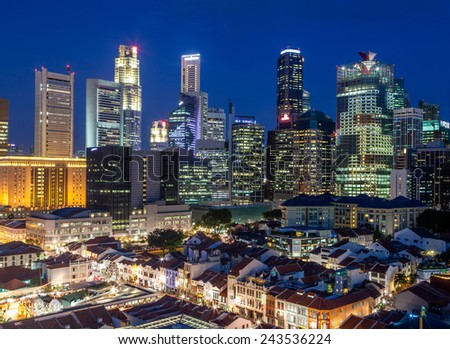 Singapore's old Chinatown at dusk against the backdrop of the city's new and vibrant financial district and skyscrapers in the background. - stock photo