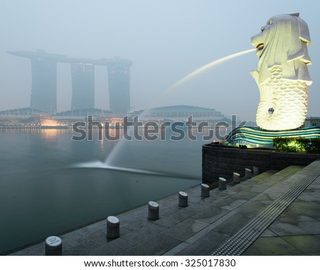 SINGAPORE-SEP 24, 2015: Haze fills the Marina Bay area. Haze is caused by the forest fire and burning of plantation in Indonesia. Also visible is the Merlion statue and Marina Bay Sands luxury hotel