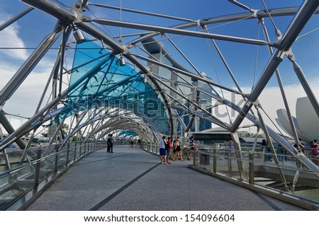 SINGAPORE - SEPT 07: The Helix Bridge and Marina Bay Sands on September 07, 2013 in Singapore. The Helix is fabricated from 650 tonnes of Duplex Stainless Steel and 1000 tonnes of carbon steel.  - stock photo