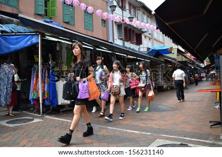 SINGAPORE-SEPTEMBER 27: Tourists shop around Chinatown, Singapore on September 27, 2013 in Singapore. Singapore's Chinatown is a world famous bargain shopping destination.  - stock photo