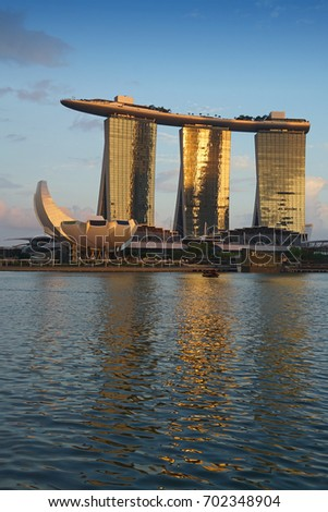 Singapore, Singapore - August 24, 2017: Sunset view at the Marina Bay district in Singapore with the iconic landmarks of The Helix Bridge, The Marina Bay Sands and The ArtScience Museum.