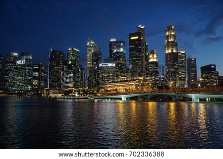 Singapore, Singapore - August 24, 2017: The highrises of the financial district, lit up at night and viewed from across Marina Bay.