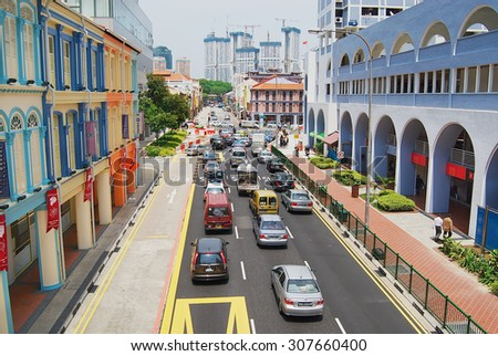 SINGAPORE, SINGAPORE - AUGUST 05, 2008: View to the colorful street with cars passing by in Singapore, Singapore. - stock photo