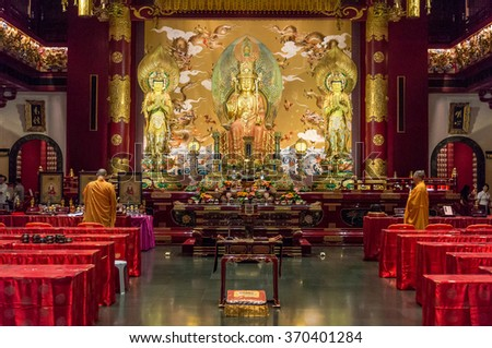 SINGAPORE/SINGAPORE - 23 DEC, 2015: Buddhist ceremony in the Buddha Tooth Relic Temple with monks. The Buddha Tooth Relic Temple and Museum was built to house the tooth relic of the historical Buddha - stock photo