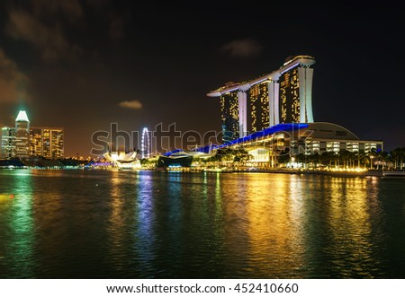 Singapore, Singapore - February 29, 2016: Marina Bay Sands Hotel and Casino of Downtown Core at night. Cityscape of luxury resort with swimming pool illuminated with light and reflected in the bay.