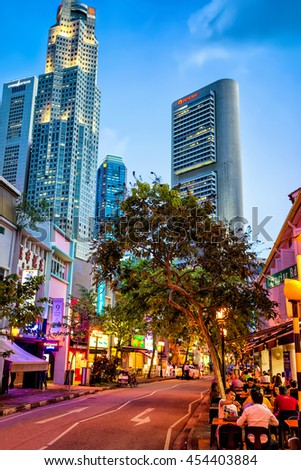 Singapore, Singapore - February 29, 2016: Shop houses at Boat Quay District and UOB Plaza of Downtown Core of Singapore skyline. United Overseas Bank is located in the Plaza. Tourists in the cafe