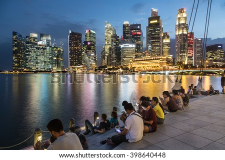 SINGAPORE, SINGAPORE - FEBRUARY 22 2016: Tourists enjoy the view on the famous Singapore skyline from the marina. Shot with long exposure to freeze the water. - stock photo