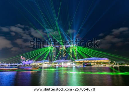 SINGAPORE, SINGAPORE - JAN 29, 2015: Marina Bay Sands hotel at night on June 29, 2015 in Singapore. Wonderful laser show, the largest light and water spectacle in Southeast Asia - stock photo
