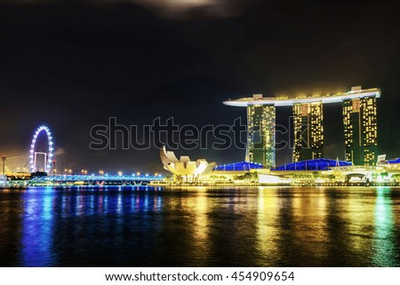 Singapore, Singapore - March 1, 2016: Singapore Flyer, Artscience museum and Marina Bay Sands Hotel and Casino of Downtown Core, Singapore at night. Cityscape of a luxury resort with swimming pool