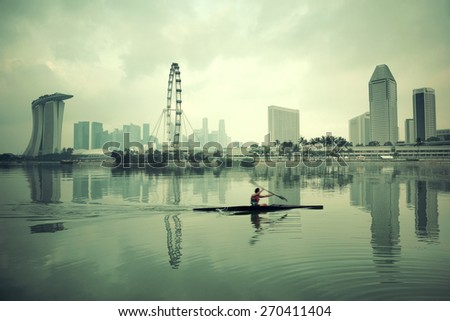 Singapore skyline with urban buildings and boat reflection over water - stock photo