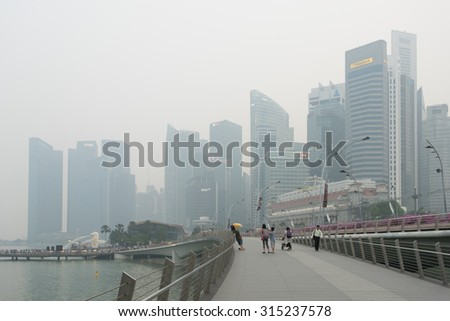 Singapore - 10th September, 2015: Haze fills the Marina Bay area. Haze is caused by the forest fire and burning of plantation in Indonesia. Also visible is the Merlion statue. - stock photo