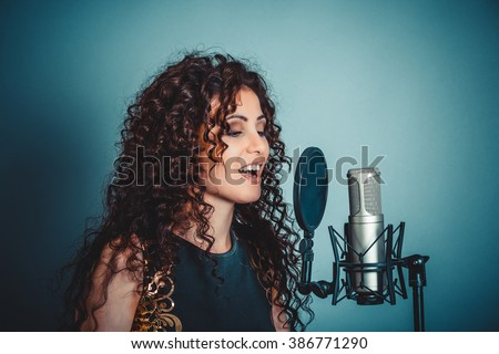 Singer. Closeup portrait head shot sexy beautiful happy young woman lady girl singing with microphone smiling isolated green background wall. Positive human emotion expression feeling life perception  - stock photo